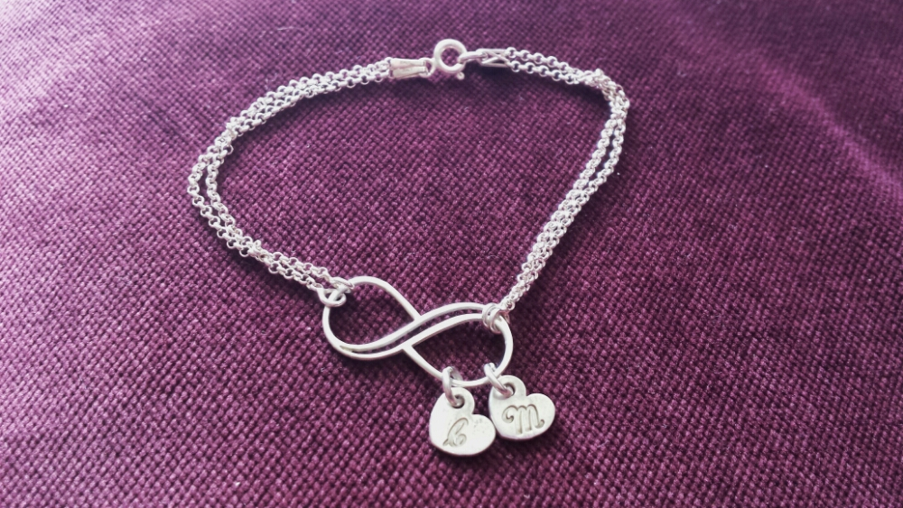 Sterling silver infinity bracelet with charms